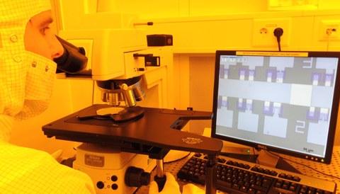 Mann überprüft hergestellte Speicherzellen mittels eines Mikroskops