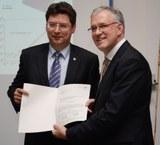 Wirtschaftsminister Reinhard Meyer überreicht Professor Eckhard Quandt den Zuwendungsbescheid für das Kompetenzzentrum Nanosystemtechnik.